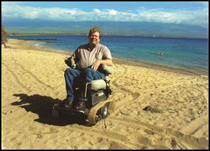 A man using a power wheelchair on the beach.