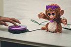 Purple switch being used to move a toy monkey