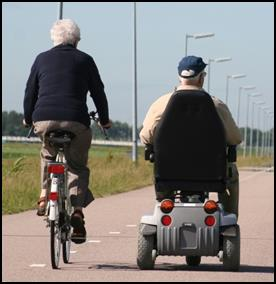 Two men (one riding a bike, the other using a power wheelchair) on a path.