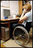 A woman in a wheelchair, using the phone in an office.