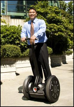 A man in business attire using a Segway.